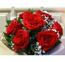 Букет из 7 красных роз (эквадор) с гипсофиллой зеленью в упаковке из бумаги крафт с большим бантом.