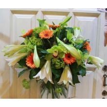 Праздничный букет из лилий лонгифлорум, калины, зеленых орхидей, оранжевых гербер с зеленью в натуральной упаковке с лентами.