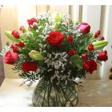 Большой праздничный букет из лилий лонгифлорум, красных роз, красных кустовых роз, лимониума, фисташки, эвкалипта на каркасе с жемчужными крупными бусинами и красным атласным бантом в связке.