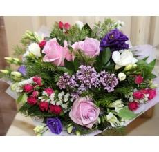 Романтический букет из розовых роз, эустомы, фрезии, кустовой малиновой розы, статицы, ветки сирени, альстромерии, пихты, зелени в натуральной упаковке с большим атласным бантом.