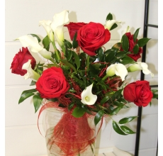 Букет из красных роз, белых калл, с красным шнуром и сизалем, итальянским рускусом в натуральной упаковке с капроновыми лентами.