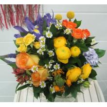 Весенний букет из желтых ранункулюсов, ирисов, вероники, кустовых роз разных цветов, оранжевых крупных роз, матрикарии, орнитогалума, краспедии, гиацинта, зелени в натуральной упаковке из сизаля с лентами