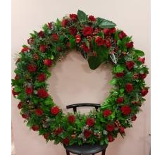 Венок на каркасе. Состав: 68 красных роз, гиперикум, аспарагус, питоспорум, рускус, эвкалипт, листья антуриума, листья алоказии с атласной траурной лентой. Диаметр 110-120 см.