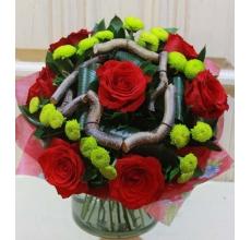 Букет из красных роз, фисташковых кустовых хризантем, веточек корилуса, аспидистры, зелени в упаковке из фетра с лентой.