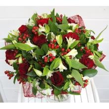 Букет из нежной альстромерии, красных роз, гиперикума, ципируса папируса, зелени в натуральной упаковке из сизаля с лентами