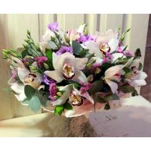 Букет из белых орхидей с фиолетовой эустомой, с лиловой статицей, зеленью в натуральной упаковке с бантом из армированной ленты.