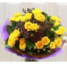 Букет из желтой кустовой розы, веток сирени, зелени в натуральной упаковке с лентами