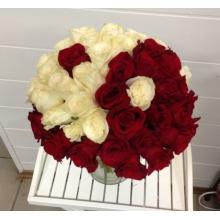 Букет из 45 красных и белых роз, выложенных в форме инь-ян с длинными ножками и широкой атласной лентой.