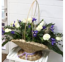 Корзина из белых роз, ирисов, листьев аспилистры, эвкалипта, зелени с декоративными элементами и лентами.