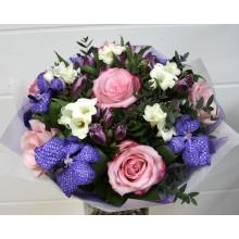 Букет из цветов голубой орхидеи ванды, розовой розы, фрезии, альстромерии, эвкалипта, зелени в натуральной упаковке с лентами.