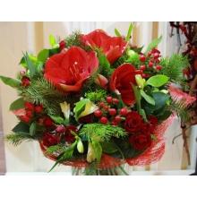 Праздничный букет из красных амарилисов, кустовых роз, гиперикума, альстромерии, веток пихты, салала в натуральной упаковке с лентами.
