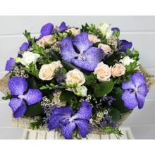 Букет из персиковой кустовой розы, цветов орхидеи ванды, белой фрезии, лимониума, восковника, зелени в натуральной упаковке с лентами