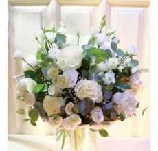 Большой букет из белой эустомы, белой розы, эвкалипта, гипсофиллы в упаковке из бумаги крафт и фетра с большим атласным бантом.