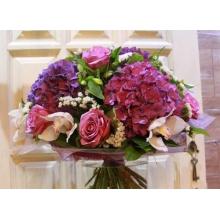 Большой букет из гортензии, белых орхидей, лиловых роз, статицы, альстромерии в натуральной упаковке из сизаля с лентами.